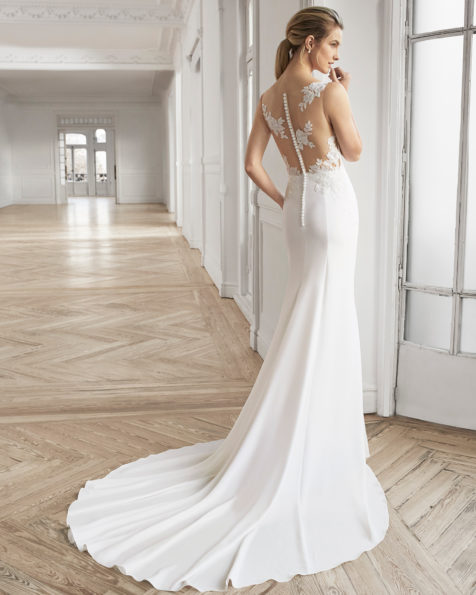 Rochie de mireasă în formă de A din georgette, dantelă și strasuri. Decolteu adânc și spate din dantelă și transparențe. Disponibilă în culoarea ecru. Colecția AIRE BARCELONA 2019.