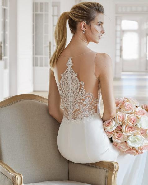 Rochie de mireasă cu croi drept din georgette, dantelă și strasuri. Decolteu iluzie cu bretea de strasuri cu spate din dantelă și strasuri. Disponibilă în culoarea ecru. Colecția AIRE BARCELONA 2019.