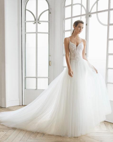 Rochie de mireasă în stil prințesă din dantelă strasuri și crep. Decolteu adânc și spate decoltat cu fustă suprapusă de tul. Disponibilă în culoarea ecru. Colecția AIRE BARCELONA 2019.