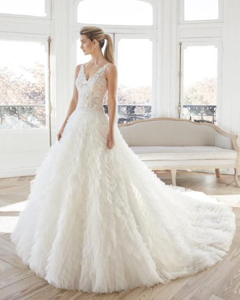 Rochie de mireasă în stil prințesă din dantelă, strasuri și volane din tul. Decolteu în V și spate decoltat. Disponibilă în culoarea ecru. Colecția AIRE BARCELONA 2019.