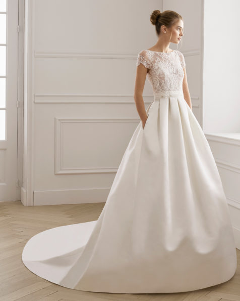 Rochie de mireasă în stil clasic din satin și dantelă strasuri. Decolteu în formă de barcă cu mânecă scurtă. Disponibilă în culoarea ecru. Colecția AIRE BARCELONA 2019.