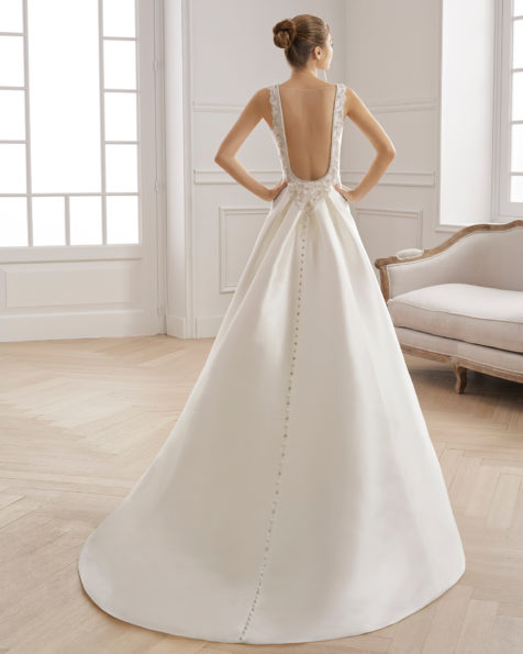 Sheath-style wedding dress in beaded tammy. Bateau neckline and low back with detachable train. Available in natural. 2019 AIRE BARCELONA Collection.