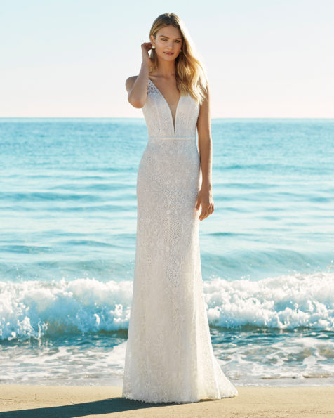 Mermaid-style wedding dress in beaded lace. Deep-plunge neckline and low back. Available in natural. 2019 AIRE BEACH WEDDING Collection.