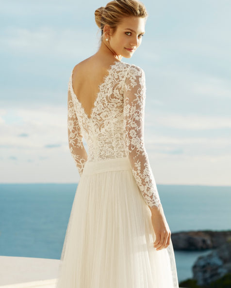 Boho-style wedding dress in soft tulle and beaded lace. V-neckline and long sleeves. Available in natural. 2019 AIRE BEACH WEDDING Collection.