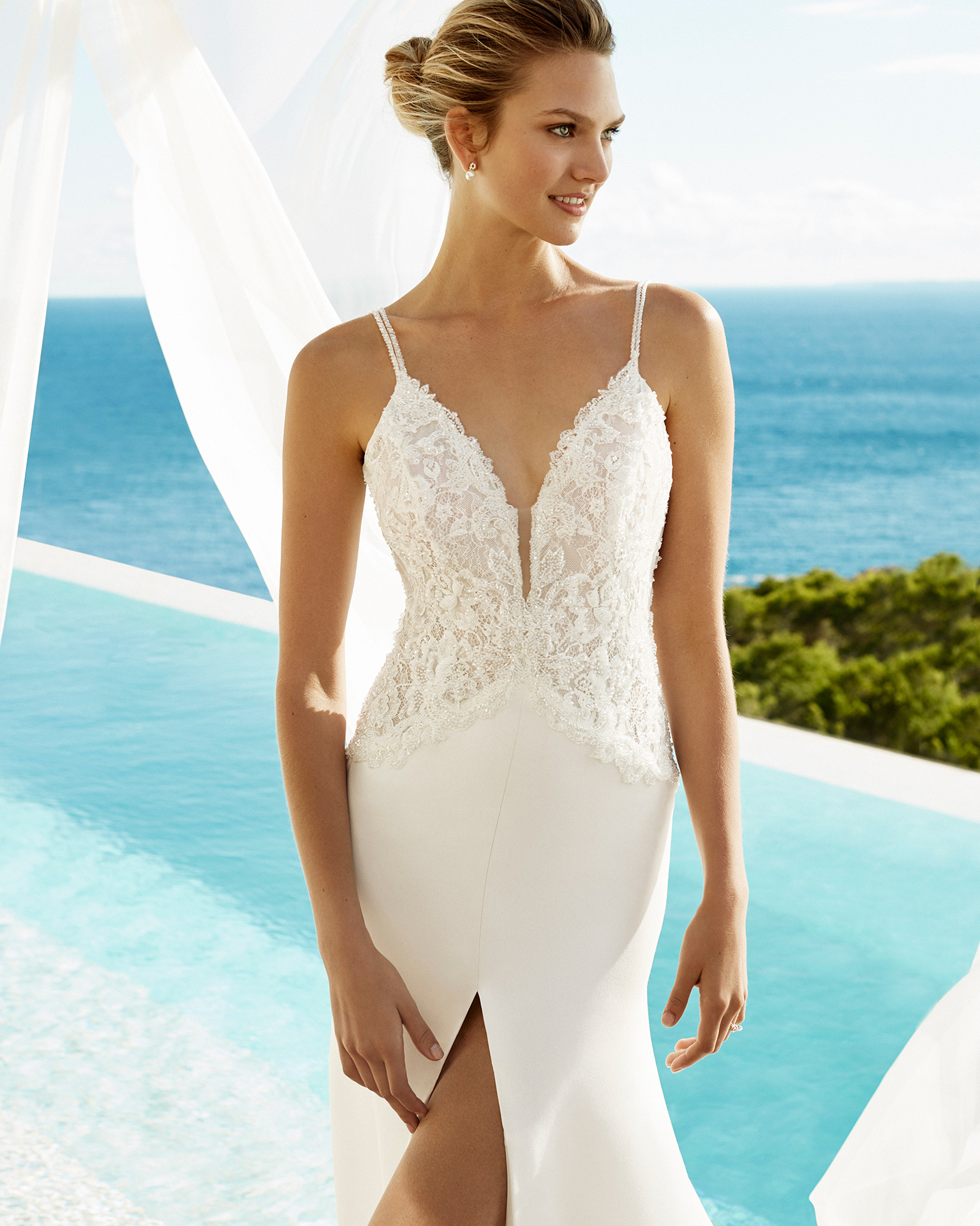 Sheath-style wedding dress in crepe and beaded lace. Deep-plunge neckline and front slit. Available in natural. 2019 AIRE BEACH WEDDING Collection.