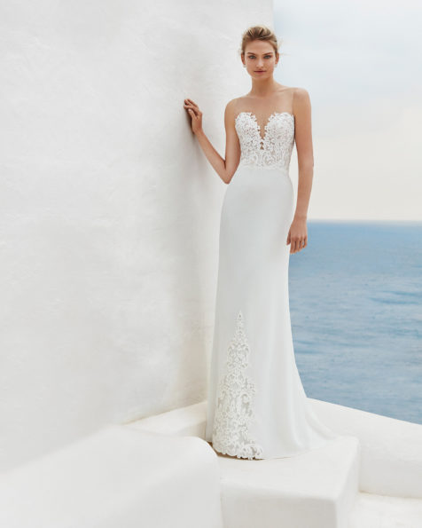 Sheath-style wedding dress in georgette crepe with lace bodice, deep-plunge neckline and low back, in natural. 2019 AIRE BEACH WEDDING Collection.