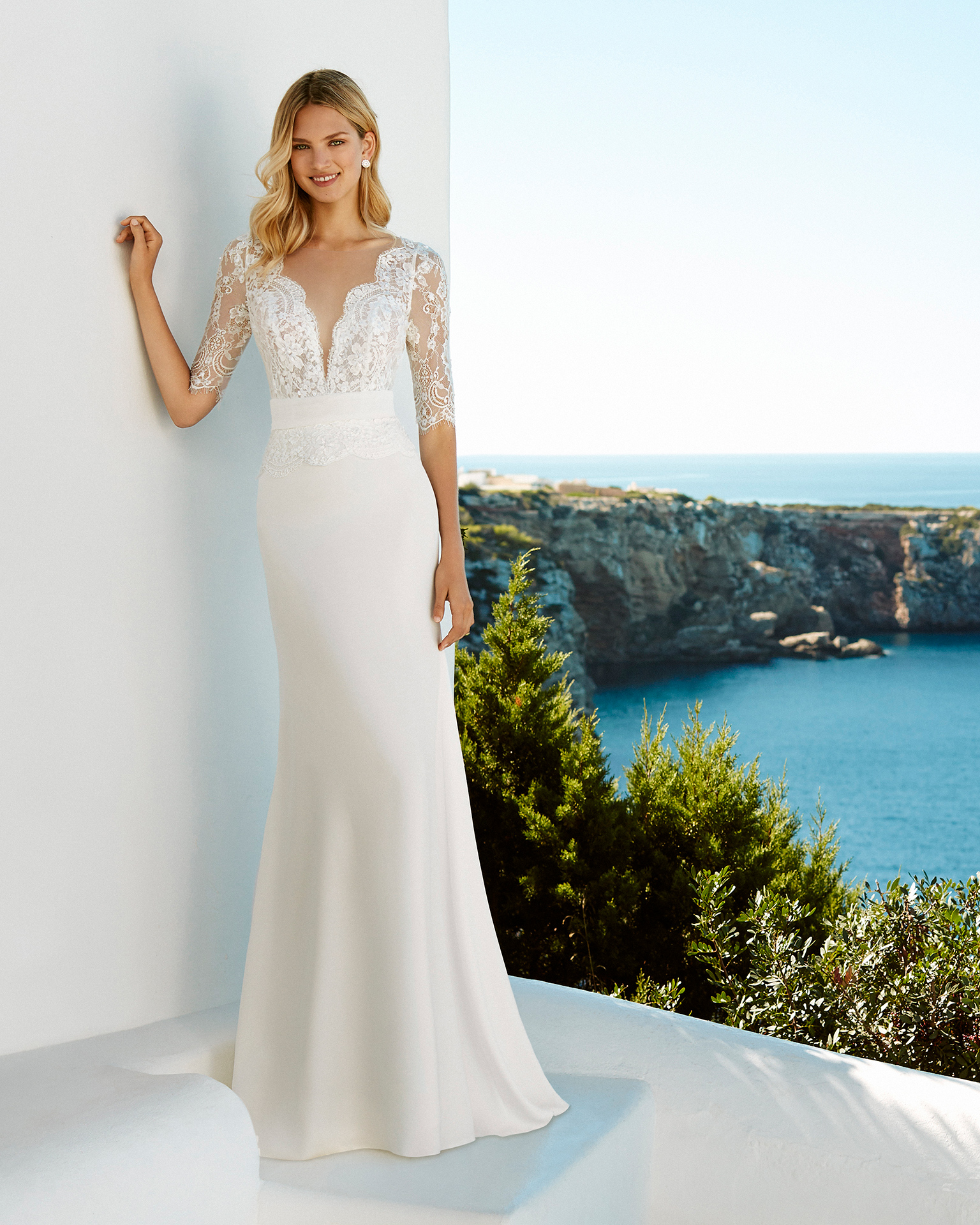 Sheath-style wedding dress in crepe and beaded lace. Deep-plunge neckline and three-quarter sleeves. Available in natural. 2019 AIRE BEACH WEDDING Collection.