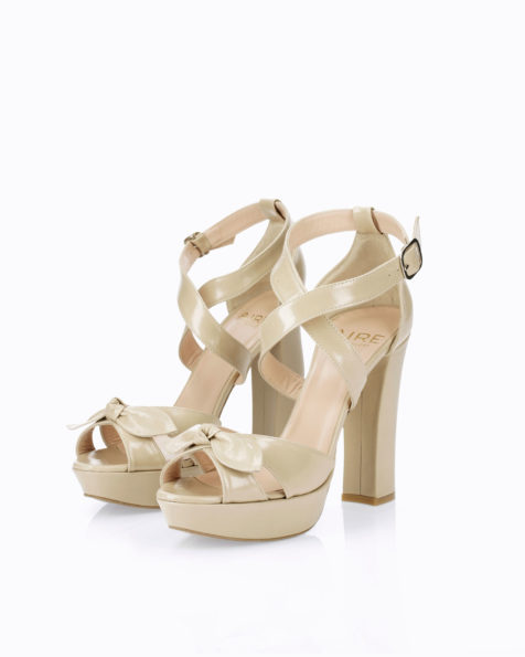 Leather bridal sandal. With high heel, closed back and bow detail. Available in natural and camel. 2019 AIRE BARCELONA Collection.
