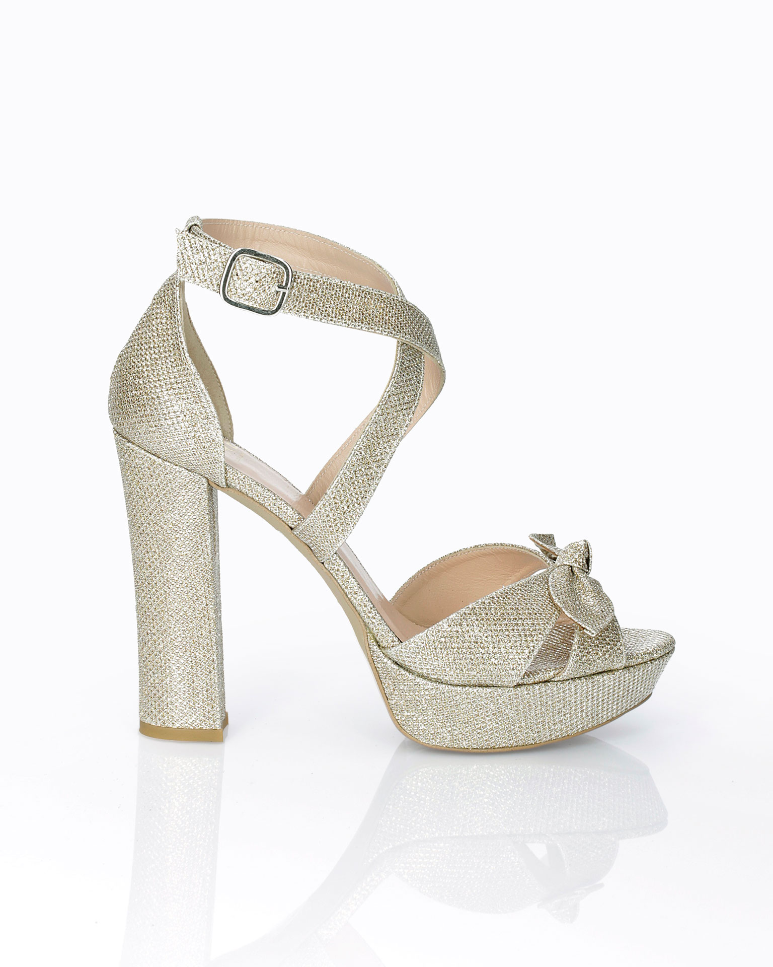 Woven fabric bridal sandal. With high heel, closed back and bow detail. Available in natural, gold and steel 2019 AIRE BARCELONA Collection.