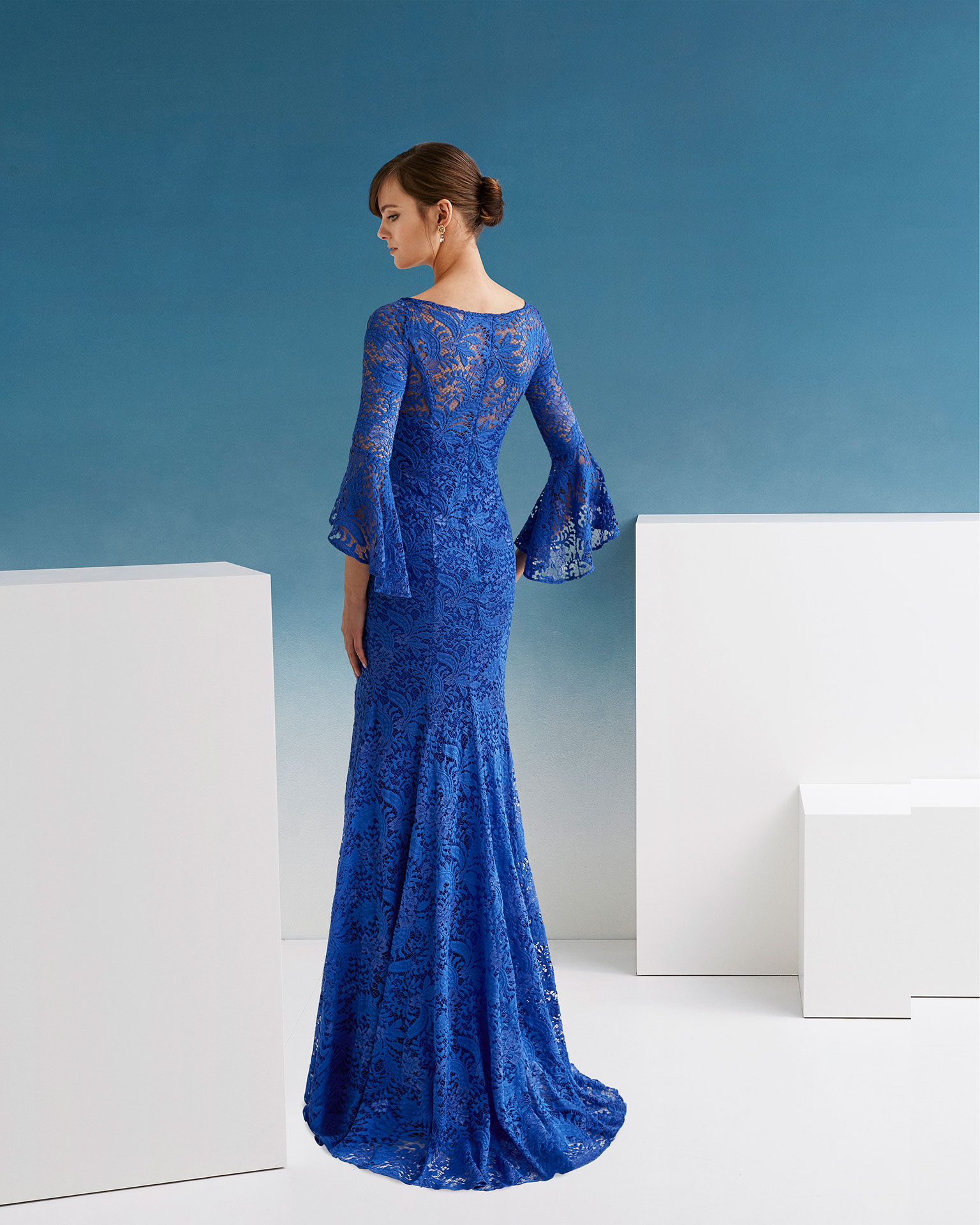 Ballgown-style lace cocktail dress. V-neckline and three-quarter sleeves with flounces. 2019 FIESTA AIRE BARCELONA Collection.