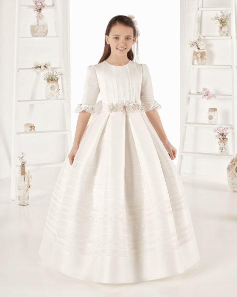 Rochie de comuniune în stil clasic cu tivuri mate fine din mătase. Cu talie normală. Disponibilă în culoarea ivoriu. Colecția AIRE COMUNION 2019.