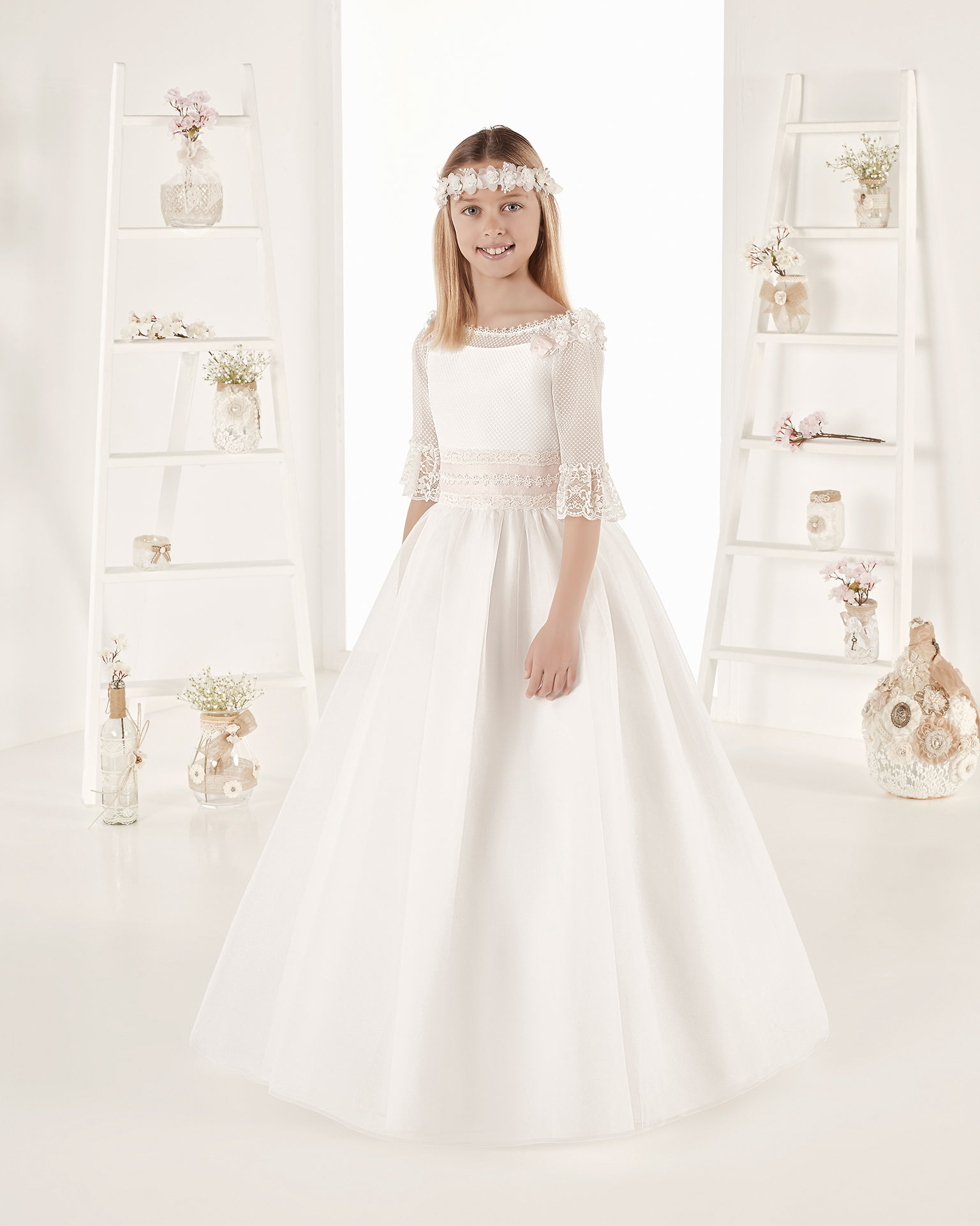 Rochie de comuniune în stil fantezie din organza reiată. Cu talie normală. Disponibilă în culoarea ecru. Colecția AIRE COMUNION 2019.