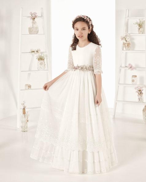 Rochie de comuniune în stil romantic din tul brodat. Cu talie scurtă. Disponibilă în culoarea ecru. Colecția AIRE COMUNION 2019.