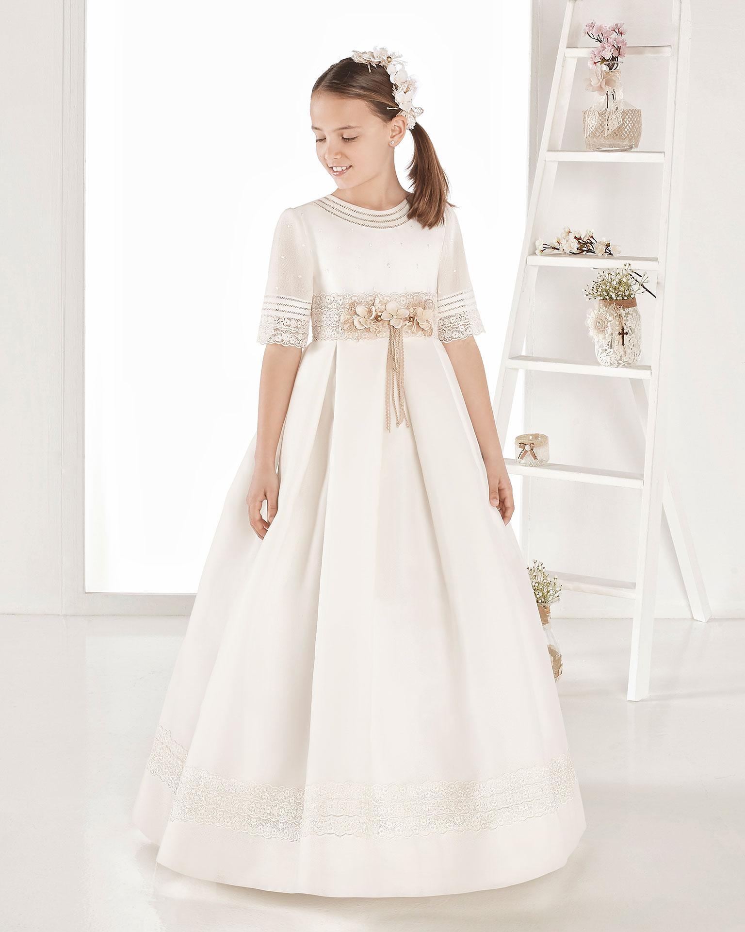 Vestido de primeira comunhão estilo clássico de tecido tipo basketweave. De corte império. Disponível em cor marfim. Coleção AIRE COMUNION 2019.