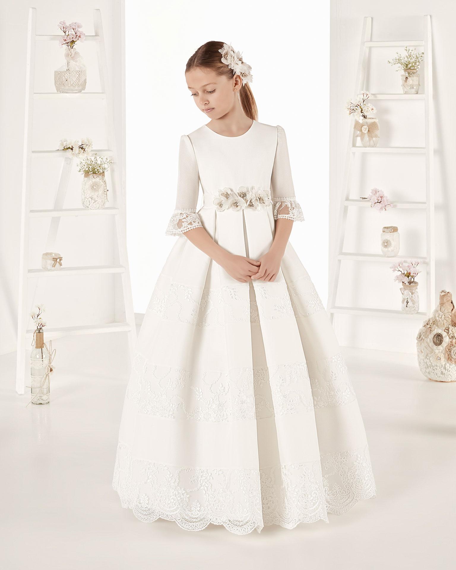 Rochie de comuniune în stil clasic mată. Cu talie scurtă. Disponibilă în culoarea ivoriu. Colecția AIRE COMUNION 2019.