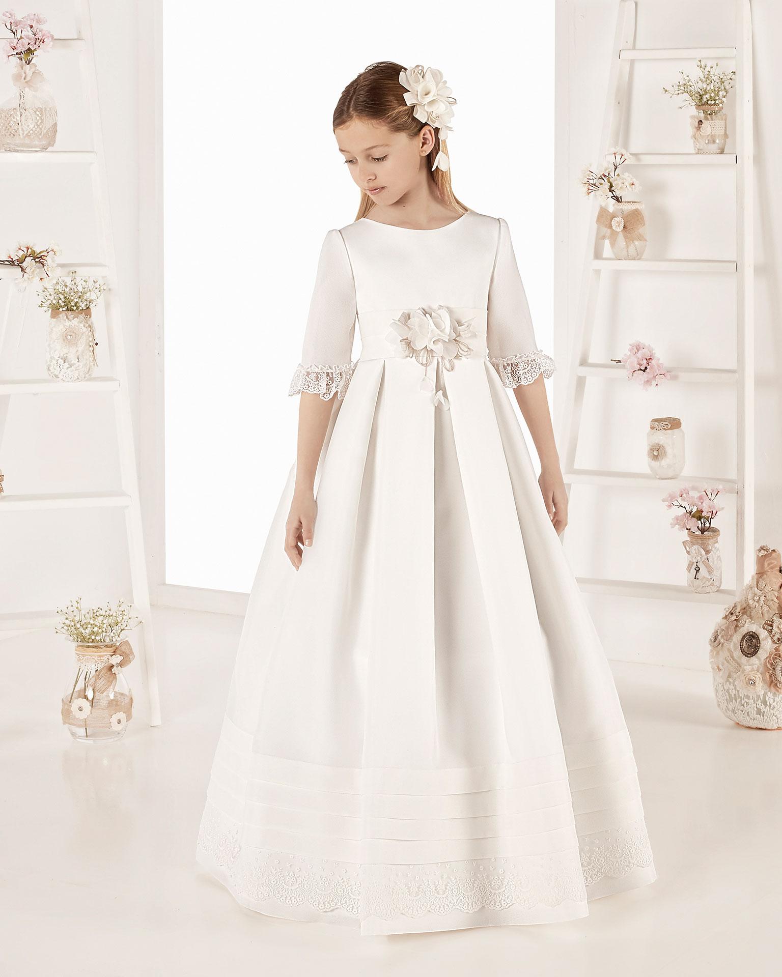 Vestido de comunión estilo clásico con lorzas en esterilla. Con talle corto. Disponible en color marfil. Colección AIRE COMUNION 2019.