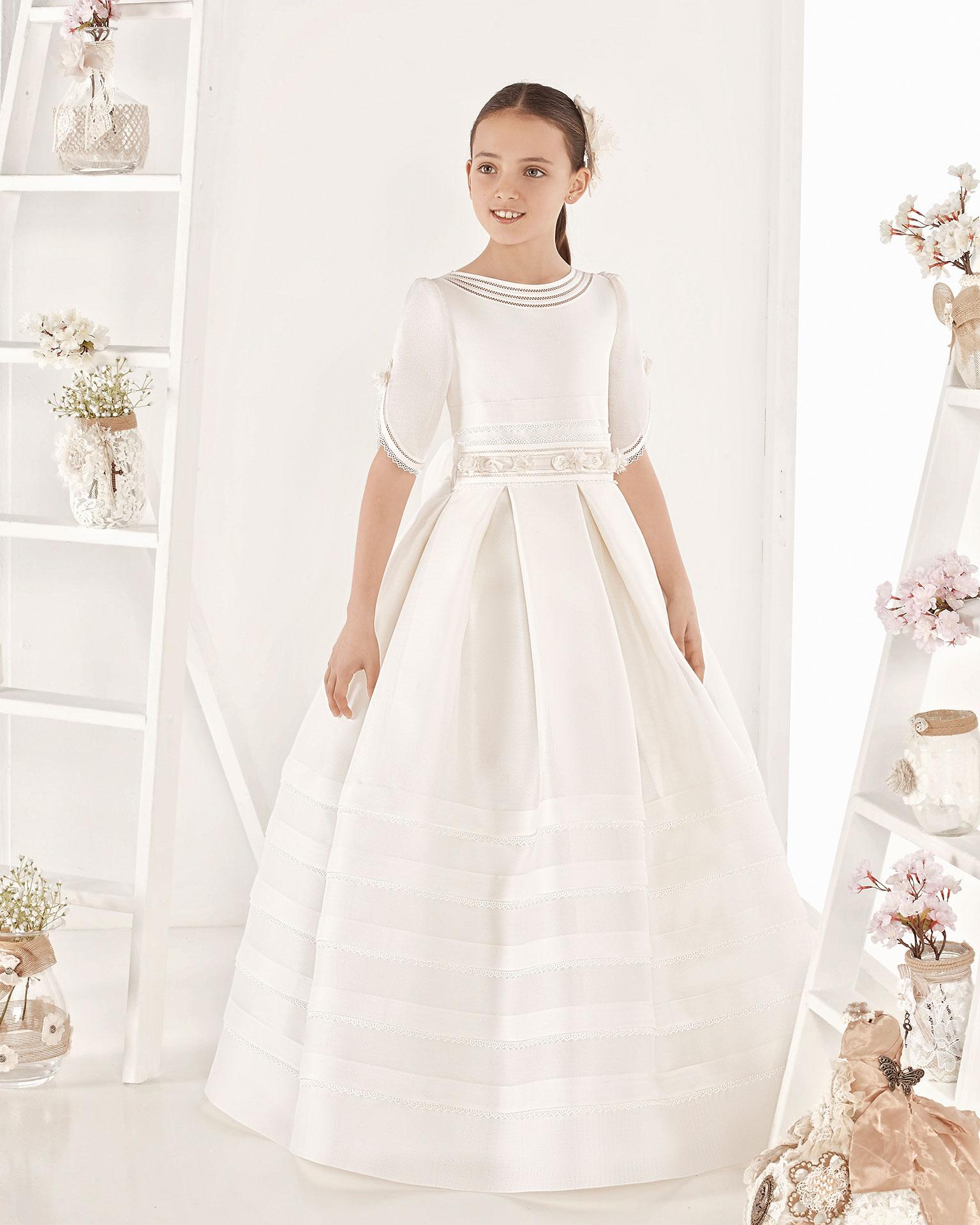 Robe de communion style classique avec plis en natté de soie fin. Avec taille normale. Disponible en couleur ivoire. Collection AIRE COMUNION 2019.