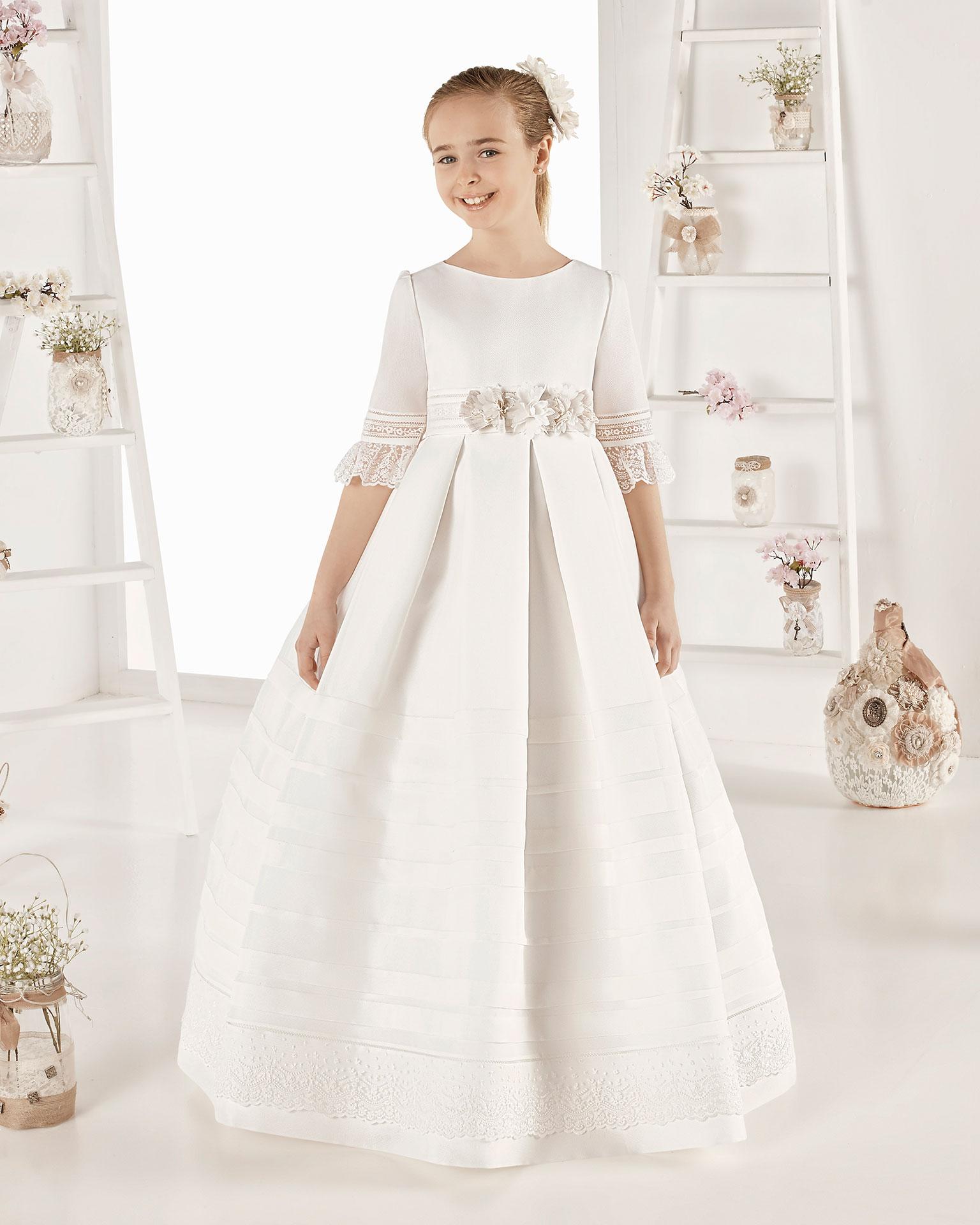 Vestido de primeira comunhão estilo clássico com pregas de tecido tipo basketweave. De corte império. Disponível em cor marfim. Coleção AIRE COMUNION 2019.